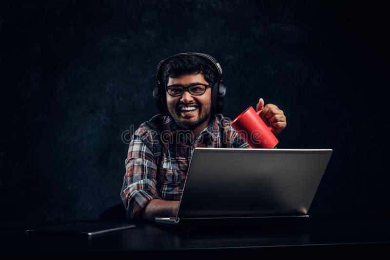 Indischer Student im Eyewear und in Kopfhörern, die eine Schale beim Sitzen am Tisch mit Laptop halten lizenzfreies stockbild