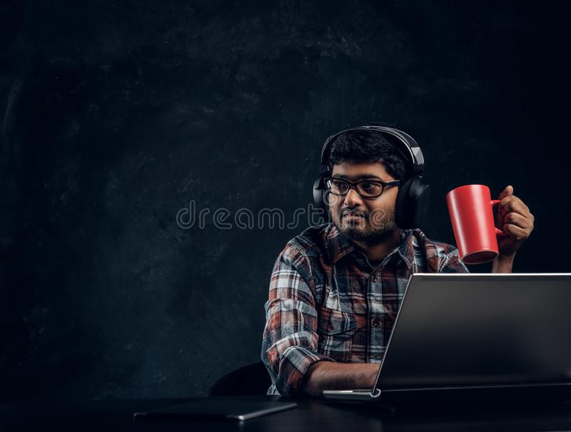 Indischer Student im Eyewear und in Kopfhörern, die eine Schale beim Sitzen am Tisch mit Laptop halten stockfotografie