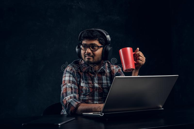Indischer Student im Eyewear und in Kopfhörern, die eine Schale beim Sitzen am Tisch mit Laptop halten stockbilder