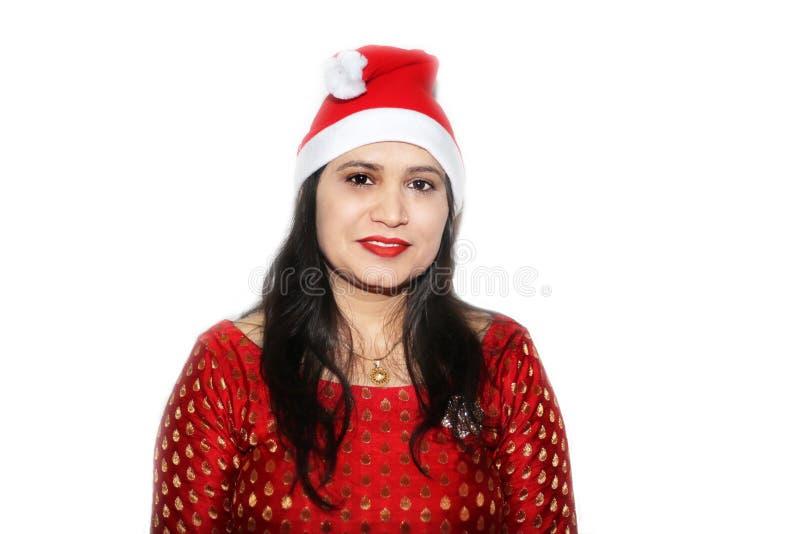 Indisches Frauenporträt im Weihnachten, das rote Kappe trägt lizenzfreie stockfotografie