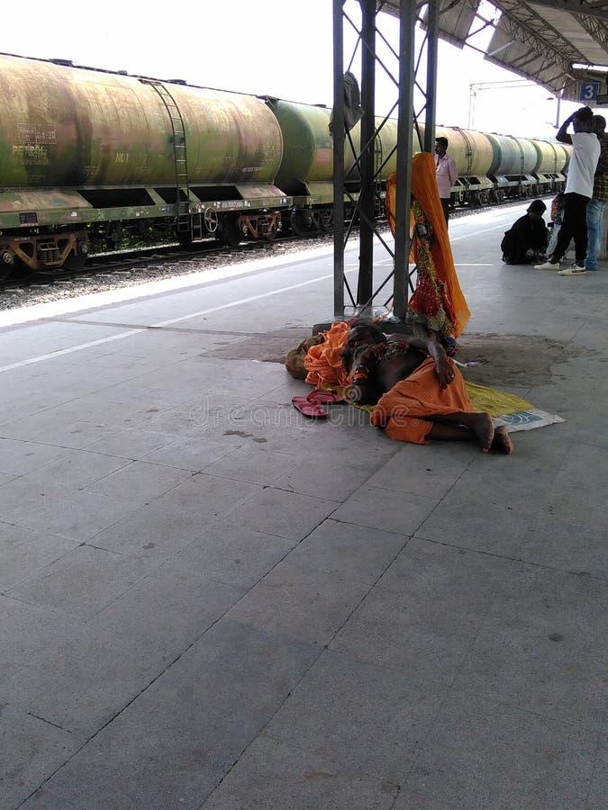 Indisches Hinduismus sadhu, das auf Bahnplattform legt lizenzfreies stockfoto