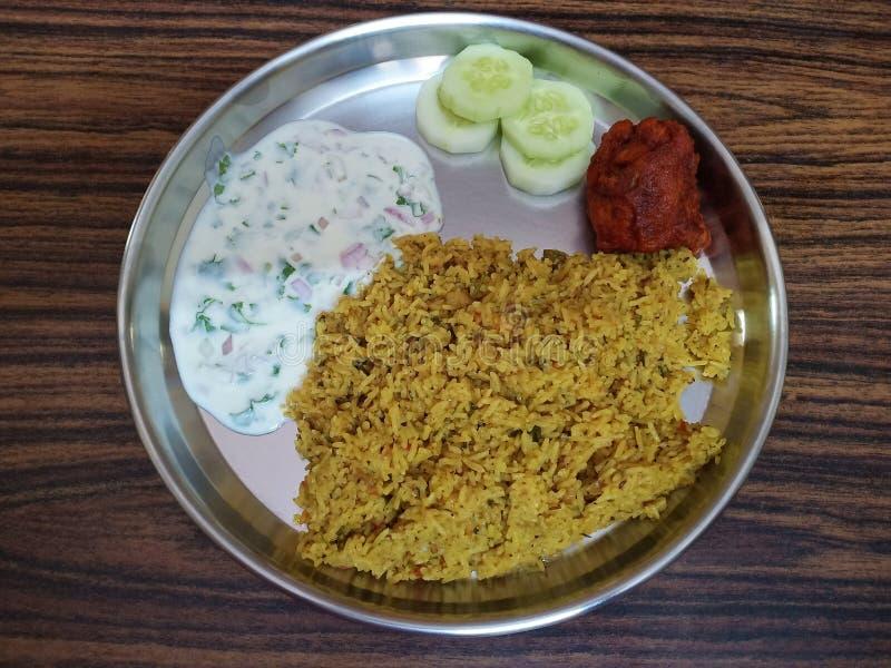Indisches Huhn-biriyani mit raita und Gurkenscheiben Kaleb lizenzfreies stockfoto