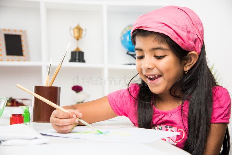 Indisches kleines Mädchen beschäftigt in der Zeichnung oder Malerei oder Farbton stockbild
