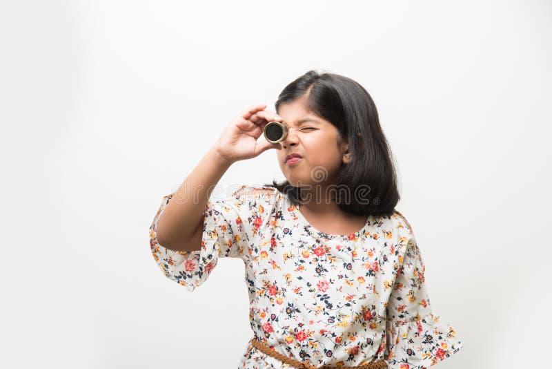 Indisches kleines Mädchen, das Teleskop verwendet und Weltraumforschung studiert lizenzfreie stockfotografie