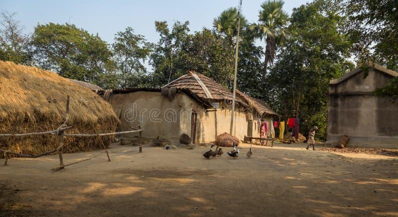 Indisches ländliches Dorf in Westbengalen mit Schlammhütten, Geflügel und Stammes- Frauen stockfoto