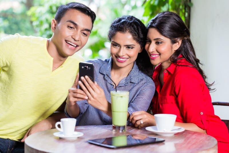 Indisches Mädchen, das den Freunden Bilder am Telefon zeigt lizenzfreie stockfotos