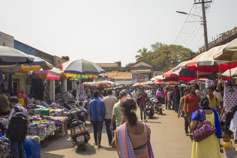 Indisches Stra?enmarkt unter sonnigen Regenschirmen, viele Leute gehen zwischen die Malle stockfotos