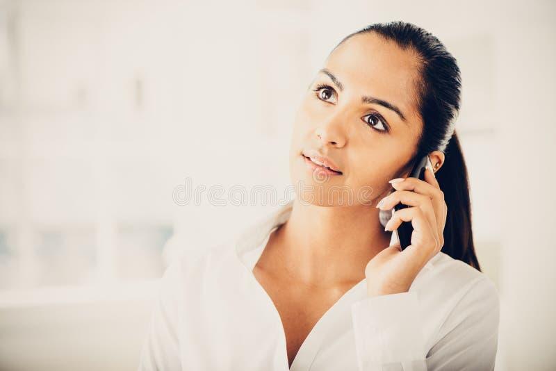 Indisk affärskvinna som använder den lyckliga mobiltelefonen arkivbild