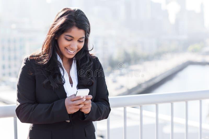Indisk affärskvinna som texting på telefonen arkivfoton