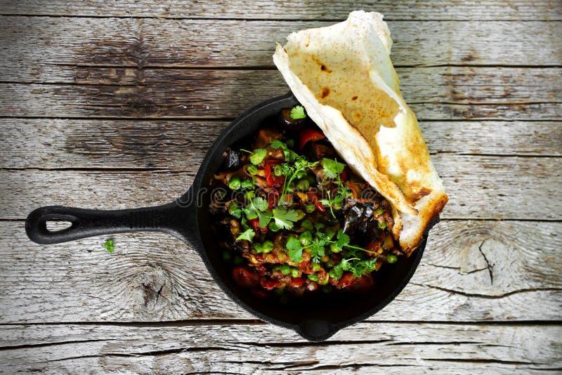 Indisk auberginecurry med ärtor och vetedosabröd royaltyfri foto