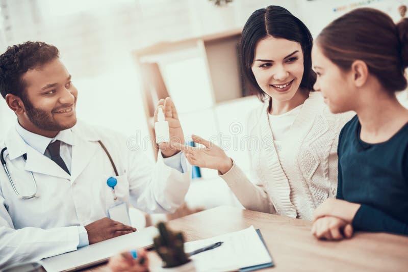 Indisk doktor som i regeringsställning ser patienter Doktorn ger modern och dottern nasal sprej arkivfoto