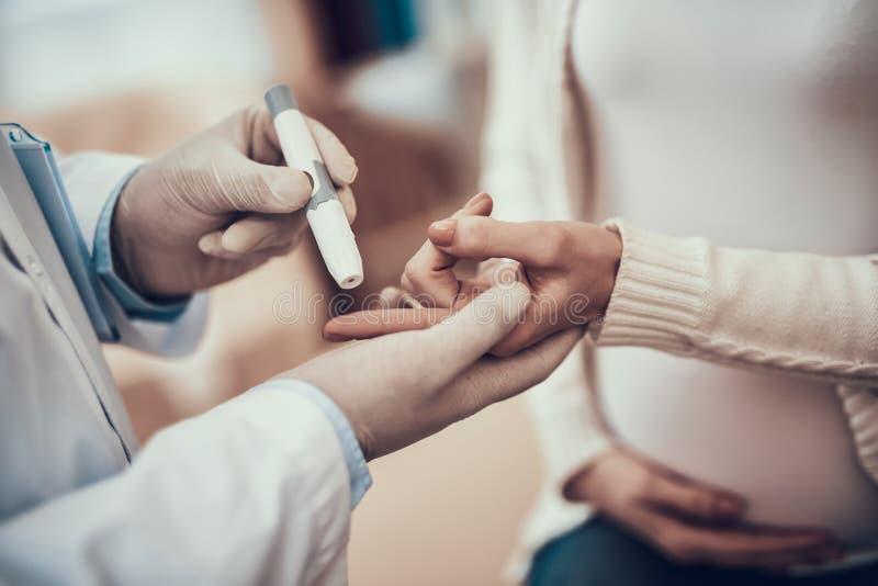 Indisk doktor som i regeringsställning ser patienter Doktorn mäter blodsocker av gravida kvinnan med dottern royaltyfri fotografi