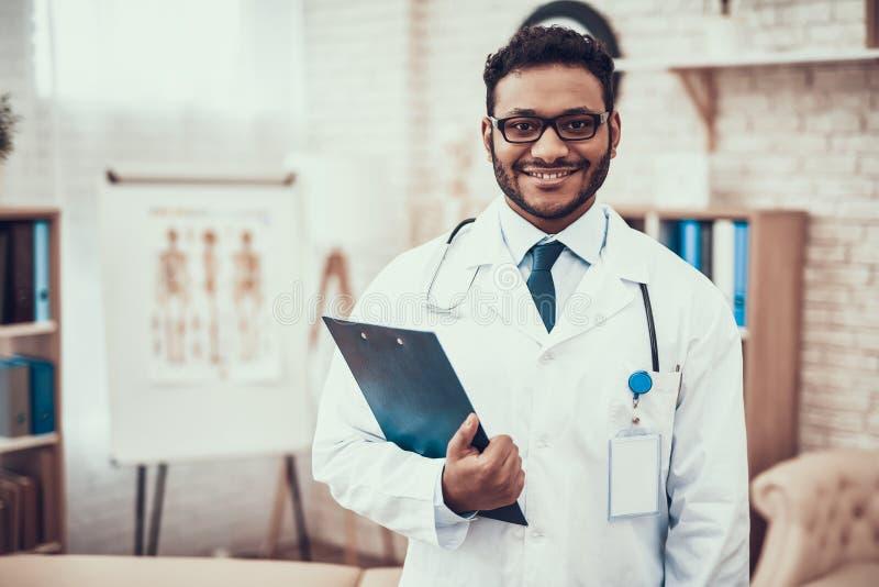 Indisk doktor som i regeringsställning ser patienter Doktorn poserar i exponeringsglas med skrivplattan royaltyfria bilder
