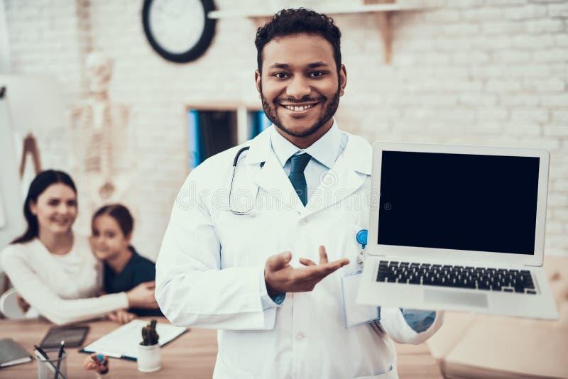 Indisk doktor som i regeringsställning ser patienter Doktorn poserar med bärbara datorn med modern och dottern i bakgrund royaltyfri bild