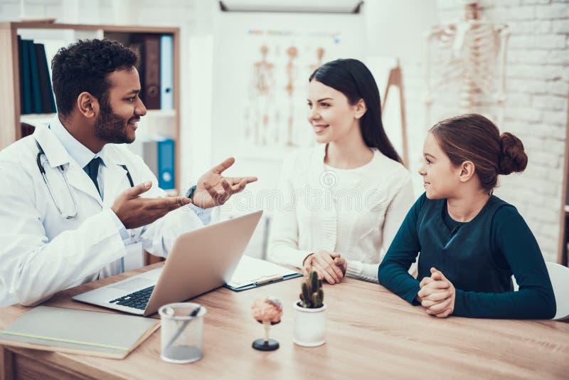 Indisk doktor som i regeringsställning ser patienter Doktorn talar för att fostra och dottern som använder bärbara datorn royaltyfria foton