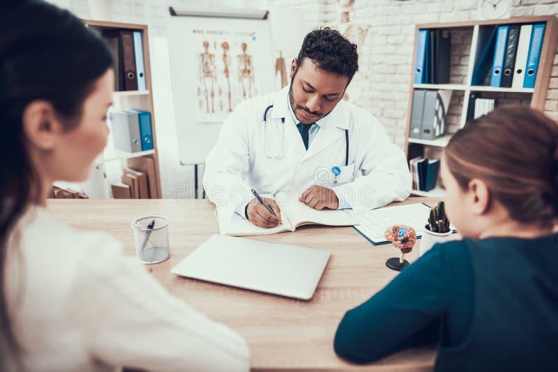 Indisk doktor som i regeringsställning ser patienter Doktorn tar anmärkningar som lyssnar för att fostra och dottern royaltyfria foton