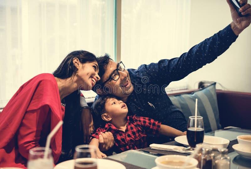 Indisk familj som tar en bild i restaurang arkivfoto