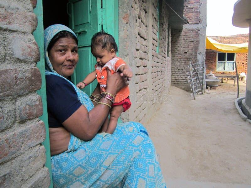 Indisk farmor som spelar med hennes barnbarn i by arkivbild