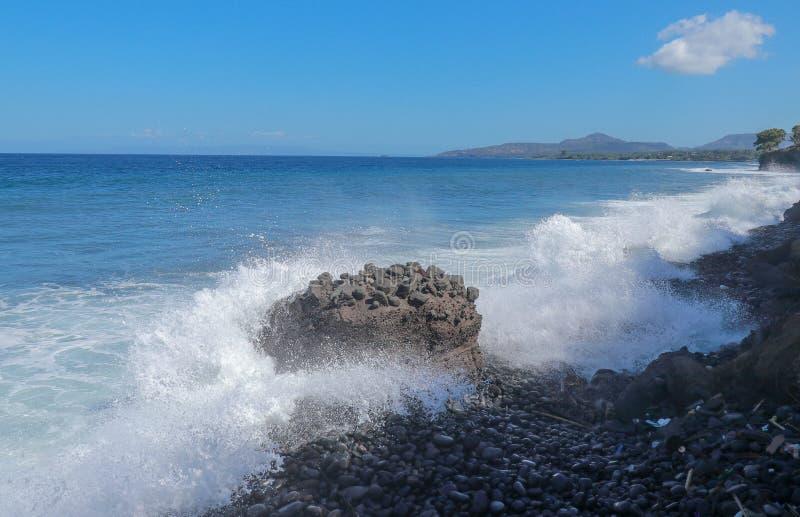 Indisk havkustlinje nära den Bali ön Stora vågor som slår den steniga stranden och anfaller de steniga kustvattensprejerna royaltyfri foto