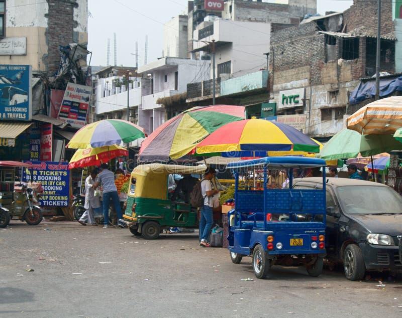 Indisk huvudsaklig basar Paharganj för gatamarknad dagströmtrick åker taxi och köpare Hindus royaltyfri foto