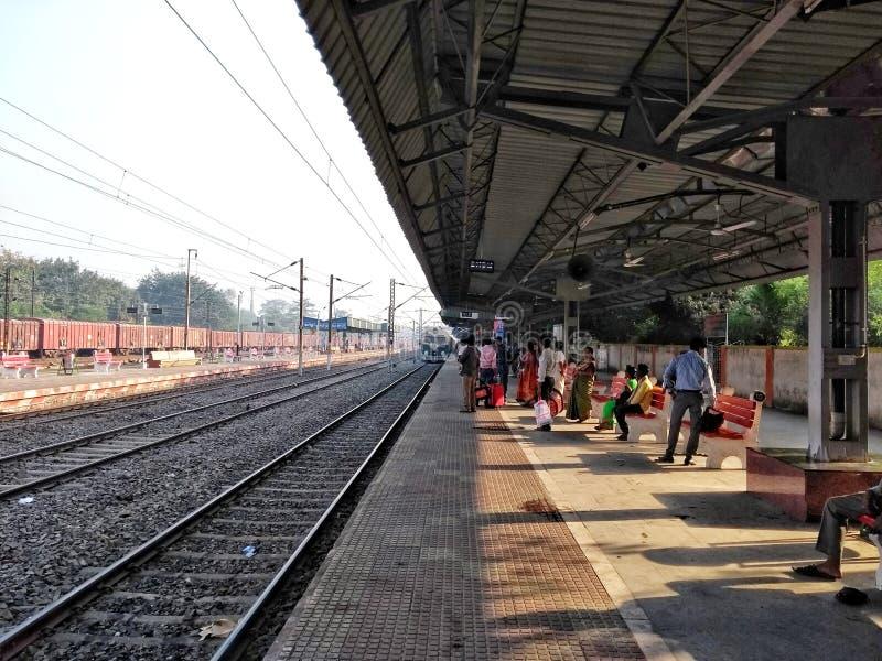 Indisk järnvägsstationplattform- och stånglinje med folkmassafolk som väntar på det inkommande drevet som ankommer royaltyfria bilder
