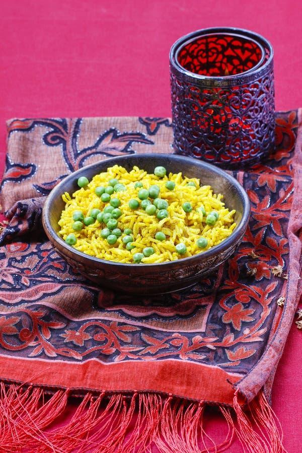 Indisk kokkonst: bunke av gula ris med gröna ärtor royaltyfria bilder