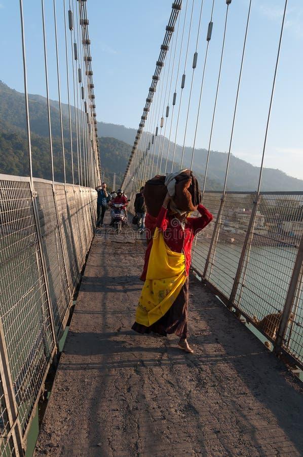 Indisk kvinna med den stora packen på den Ram Jhula bron arkivbild