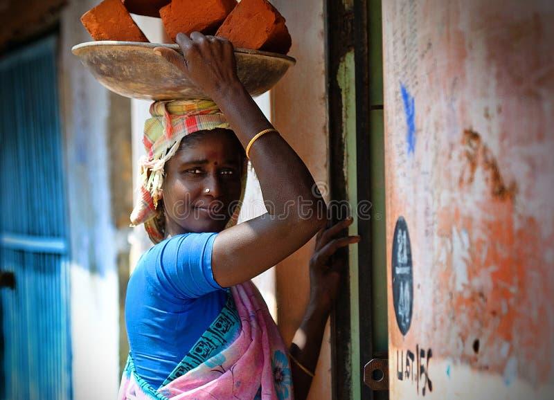 Indisk kvinna med tegelstenar royaltyfria bilder