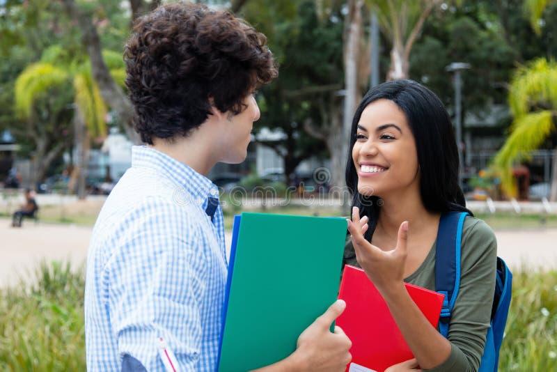 Indisk kvinnlig student som talar med den caucasian manliga studenten royaltyfri bild