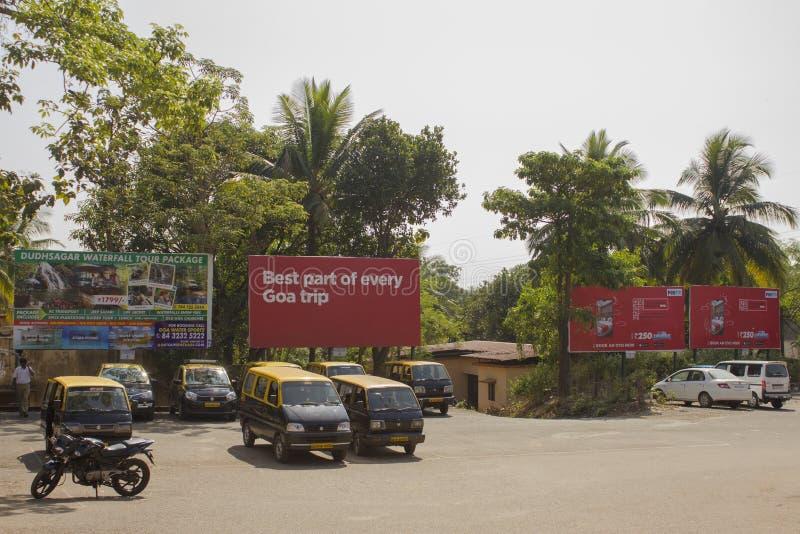 Indisk lantlig taxi som parkerar med svarta och gula bilar på en bakgrund av gröna träd royaltyfria foton