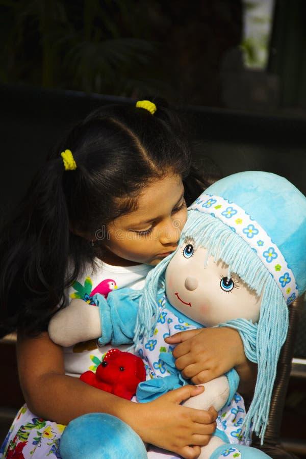 Indisk liten flicka som sitter och kysser hennes docka inom trädgården, Pune arkivfoton