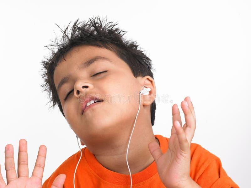 indisk lyssnande musik för pojke till royaltyfria bilder
