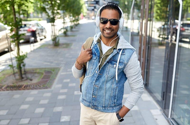 Indisk man i hörlurar med ryggsäcken i stad fotografering för bildbyråer