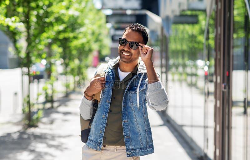 Indisk man i solglasögon med ryggsäcken i stad arkivfoto