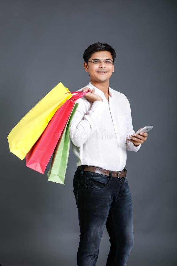 Indisk man med shoppingp?sar och uppvisning av den mobila sk?rmen royaltyfria bilder