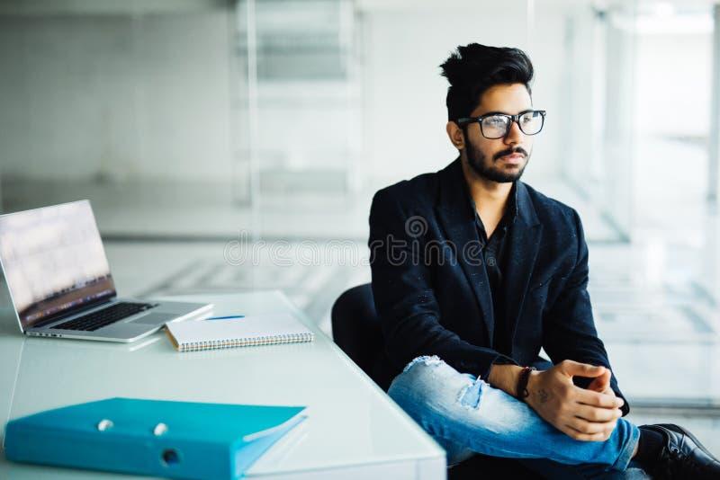 Indisk man som arbetar på datoren i modernt kontor arkivfoton