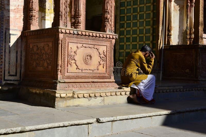 Indisk man som sitter nära den hinduiska templet royaltyfri bild