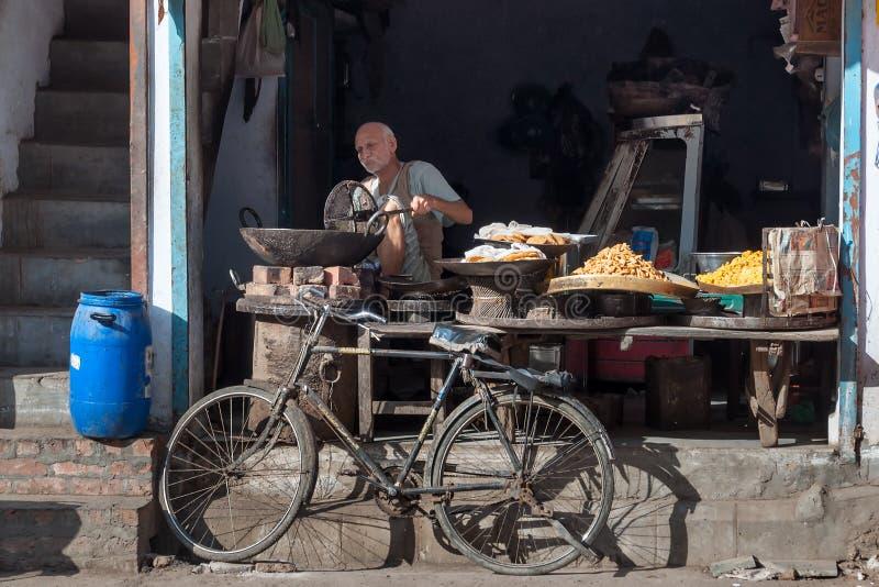 Indisk marknadsförsäljarematlagning och säljamellanmålet i lokal gata shoppar royaltyfri bild