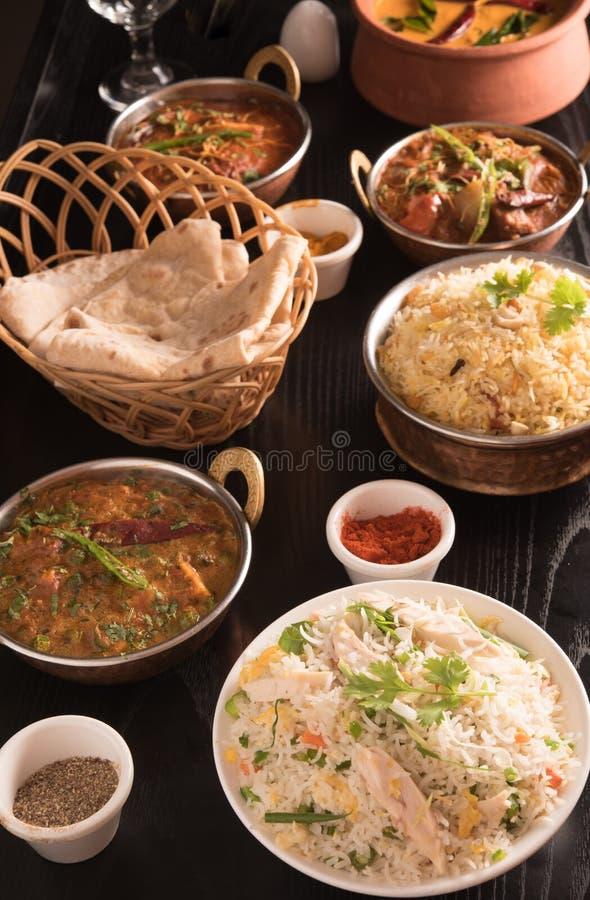 Indisk mat; curry, chapathi, stekte ris och biriyani på en svart marmorbakgrund arkivbild