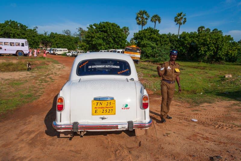 Indisk polis bredvid en bil som övervakar en beröm för öppen luft royaltyfri bild