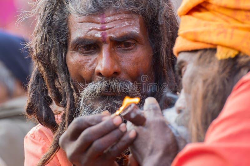 Indisk sadhus som upp tänder och röker Ganja arkivbild