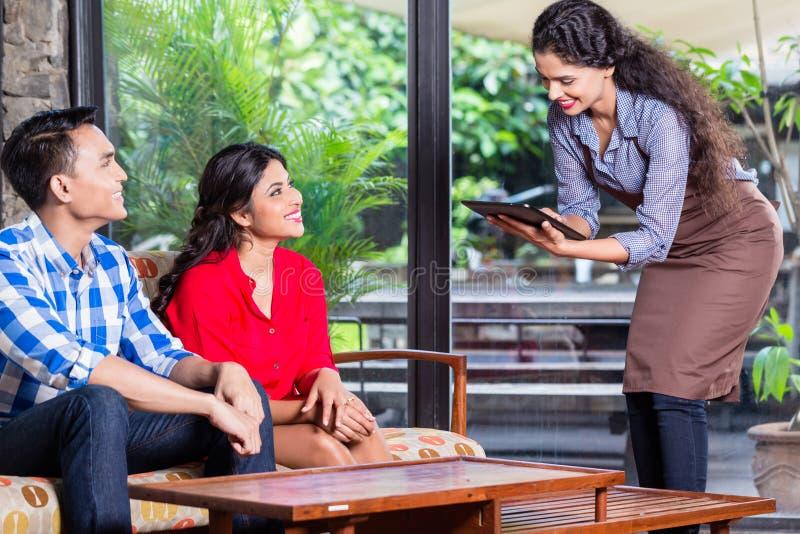 Indisk servitris som tar beställningar i kafé eller restaurang arkivbild
