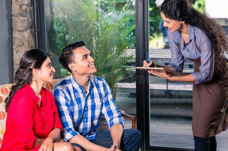 Indisk servitris som tar beställningar i kafé eller restaurang royaltyfria foton