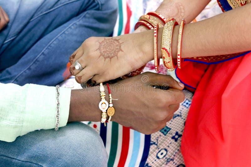 Indisk ung syster som binder rakhi på broders handled royaltyfria foton