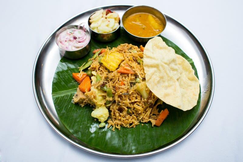 Indisk vegetarisk mat med stekte ris på bananbladmagasinet arkivbild