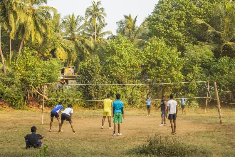 Indiska grabbar som spelar volleyboll utomhus på ett grönt djungelfält arkivfoto