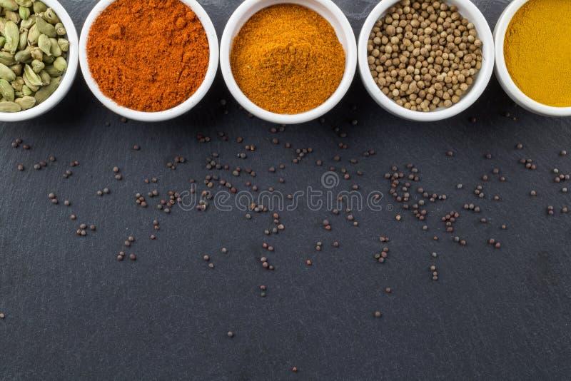 Indiska kryddor i små vita bunkar på svart bakgrund - foto för bästa sikt royaltyfria bilder