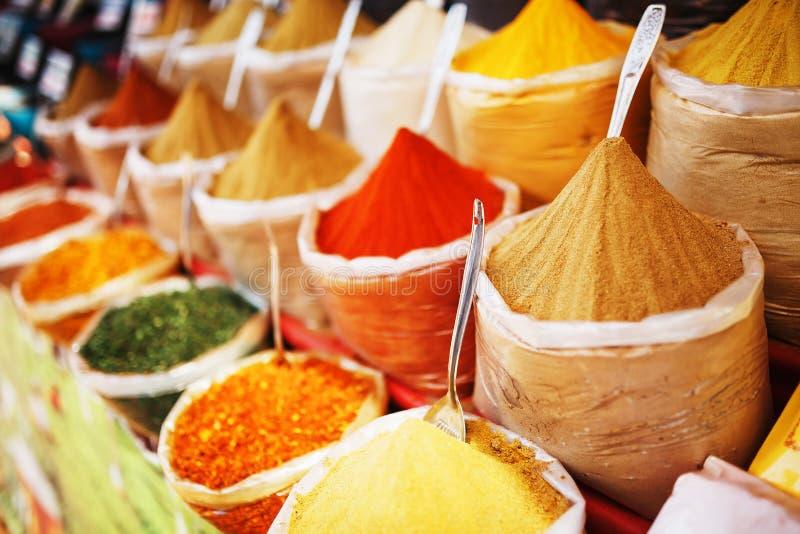 Indiska kulöra kryddor på den lokala marknaden En variation av kryddor av olika färger och skuggor, anstrykningar och texturer på arkivbild