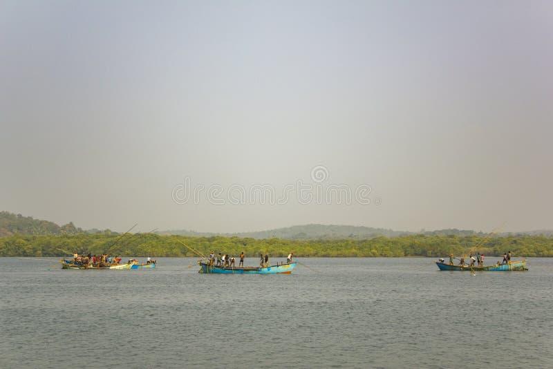 Indiska män i fartyg bröt flodsand mot bakgrunden av floden och den gröna skogen, arkivfoto