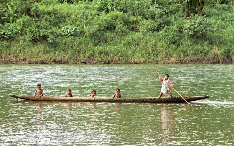 Indiska pojkar seglar med dugoutkanoten på floden, Nicaragua arkivbild